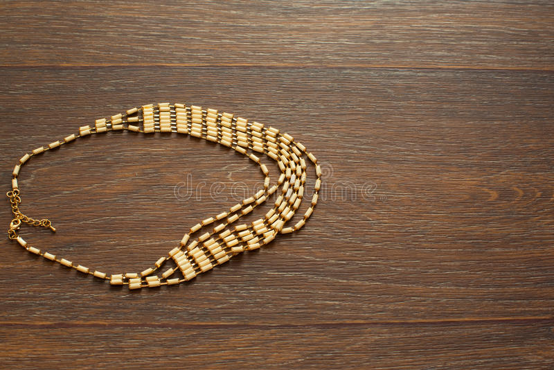 Metal necklace for women on brown wooden background. royalty free stock photo
