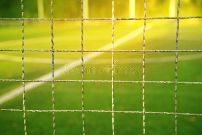 Metal net with blur green football or soccer summer field with w stock photos