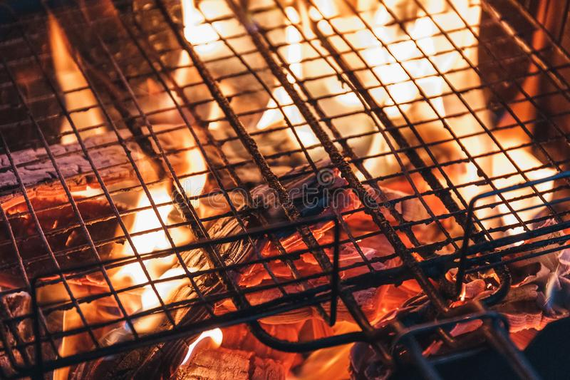 Metal net over fire burning coal ember wood in barbecue grill at stock image