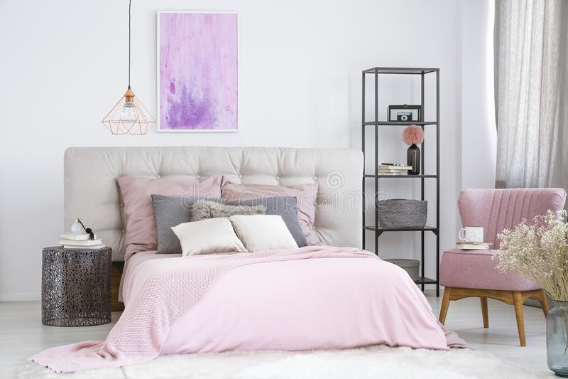 Metal nightstand next to bed. Metal designer nightstand next to wide pink bed and black industrial rack with glass shelves in bedroom stock photos