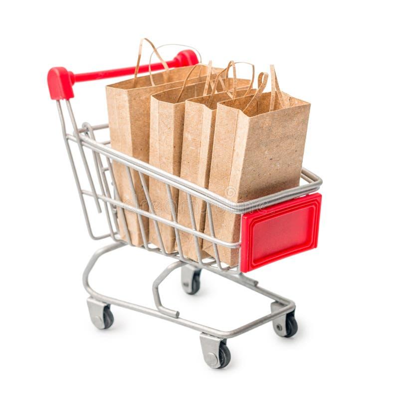 Metal o carrinho de compras com o saco de papel do ofício isolado no backg branco fotos de stock royalty free