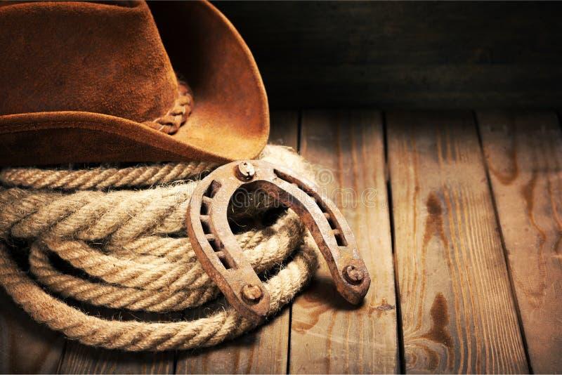 Metal o chapéu da ferradura e de vaqueiro na tabela de madeira fotografia de stock royalty free
