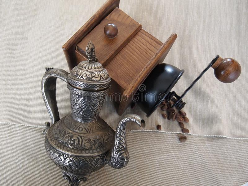 Metal o moedor do moeda-potenciômetro e de café com feijões de café fotografia de stock