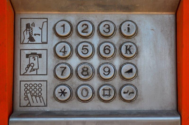 Metal o painel de um payphone da rua com botões e três pictograma com instruções para o uso fotos de stock