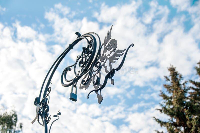 Metal o símbolo do anjo-um da felicidade da família nas ruas da cidade contra o céu nebuloso A tradição da suspensão trava o novo imagem de stock