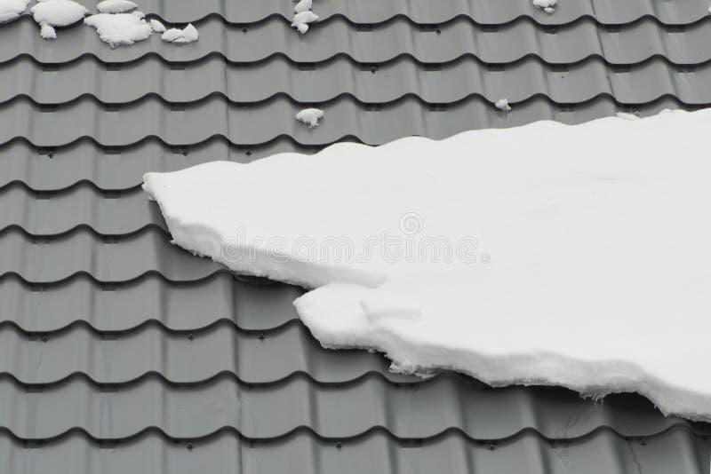 Metal o telhado de telha na estação coberta com a neve, textura do inverno do fundo Close-up fotos de stock royalty free