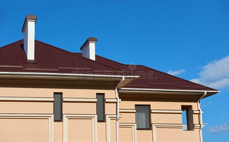 Metal o telhado e as paredes da casa privada nova, com chaminés e ventilação no fundo do céu, o conceito da construção, família c foto de stock royalty free