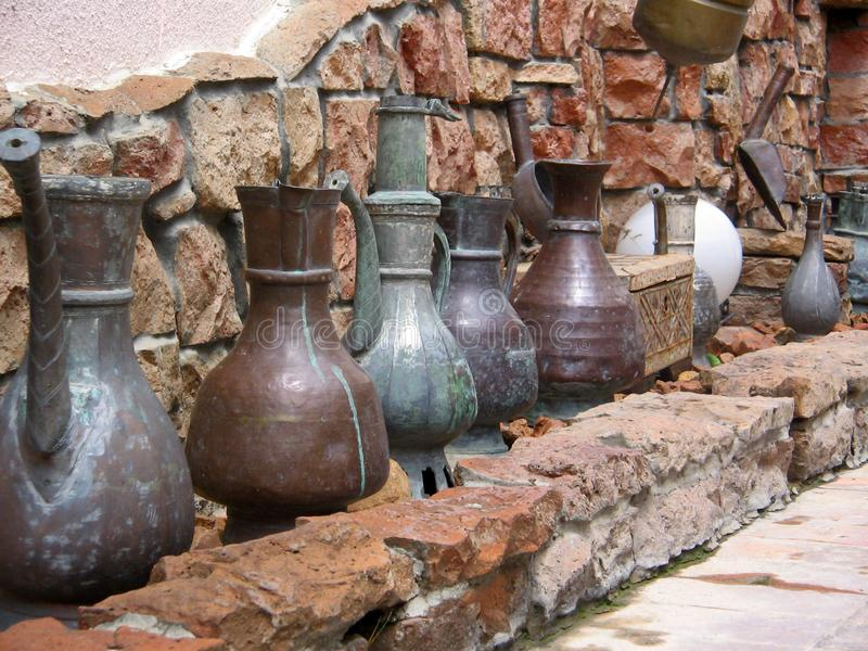 Metal, old jugs. There were metal, ancient jugs standing at the entrance on the floor in one of Samarkand`s hotels royalty free stock photography