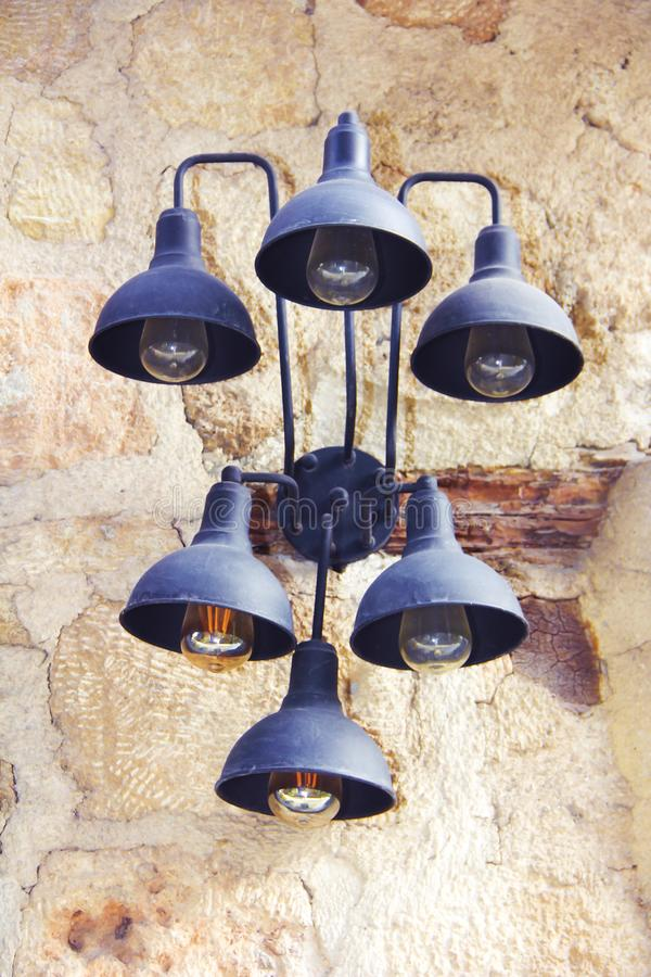 Metal old wall lamp with blue shades on a stone wall background. Metal old wall lamp with blue shades on a stone wall a background royalty free stock image
