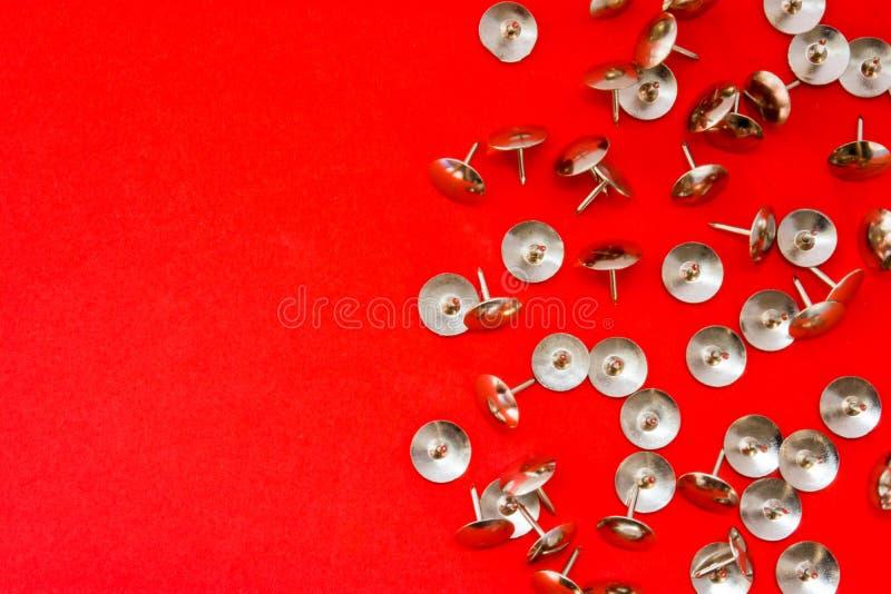 Metal os pinos ou os thumbtracks afiados brilhantes dispersados no fundo vermelho com área limpa da foto para etiquetas ou encabe fotos de stock royalty free