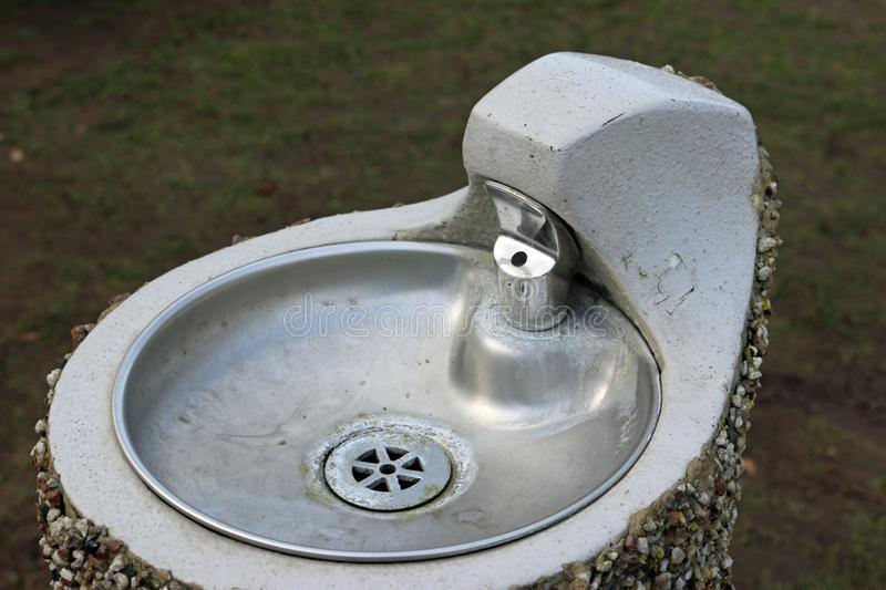 Park drinking fountain. Metal park drinking fountain with bowl on a concrete plinth with a pebble dashed exterior royalty free stock photos