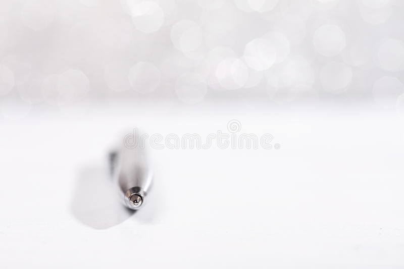 Metal pen on sparkle background. Stylish metal pen lying on white surface, on silver sparkle background royalty free stock image