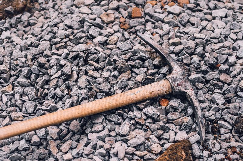 Metal pickaxe on a wooden handle on a pile of small rubble. Dirt royalty free stock image
