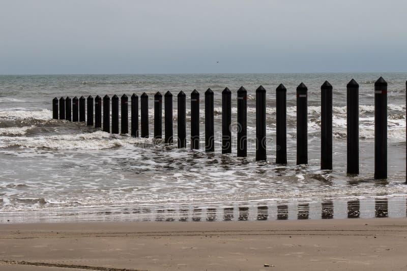 Metal pilhas da linha costeira no oceano imagem de stock