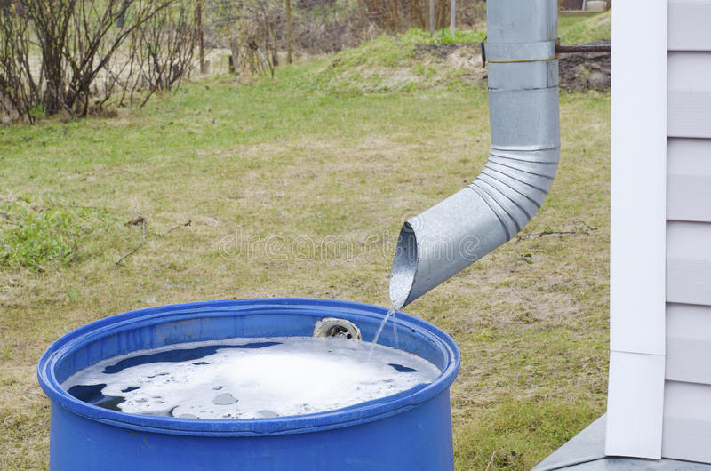 Metal pipe blue barrel. Of a metal tube for draining the water flows rainwater in a plastic blue barrel on the background of green grass in a country house royalty free stock photos