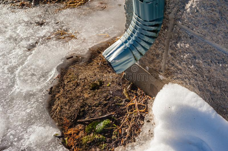 Metal pipe dripping water on melting snow. royalty free stock image