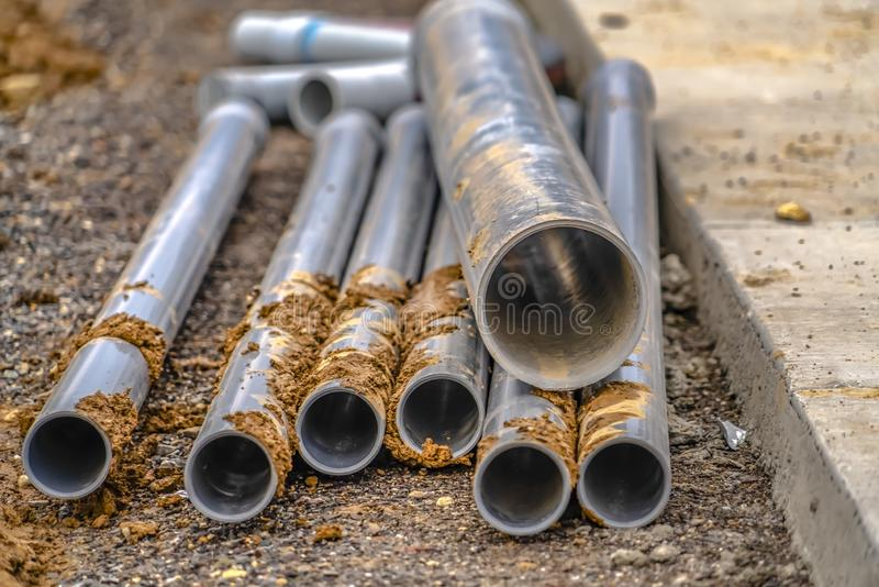 Metal pipes on a construction site in Utah Valley. Metal pipes lying on a rocky ground beside a pavement on a contruction site in Utah. Close up view of stock photography