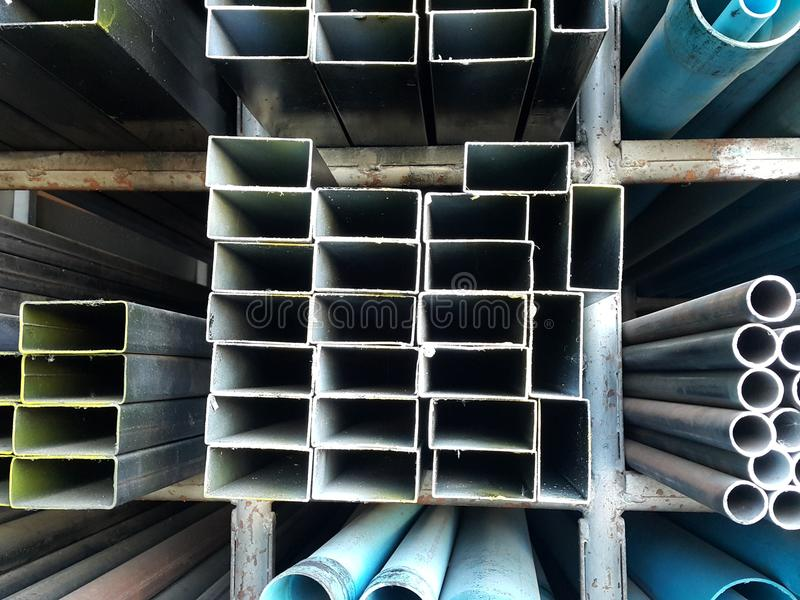 Metal pipes and pvc pipes stack on shelf stock images