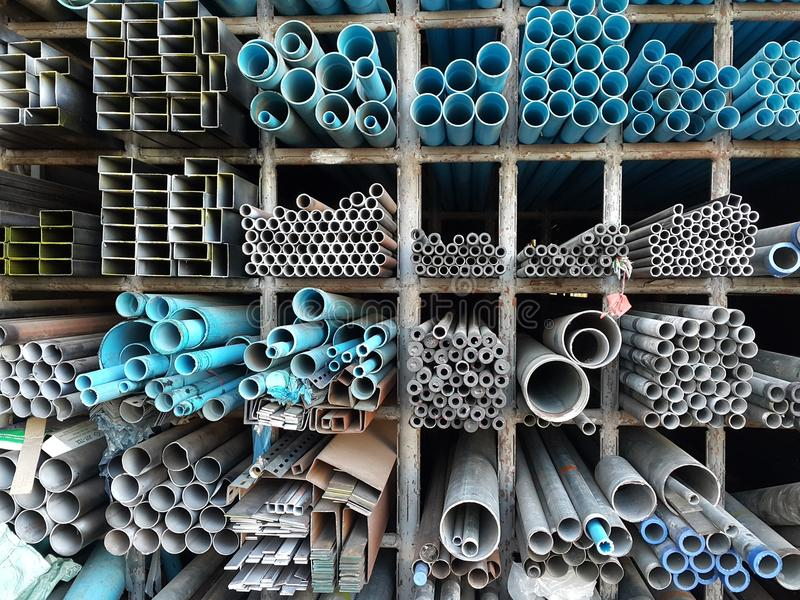 Metal pipes and pvc pipes stack on shelf royalty free stock photography