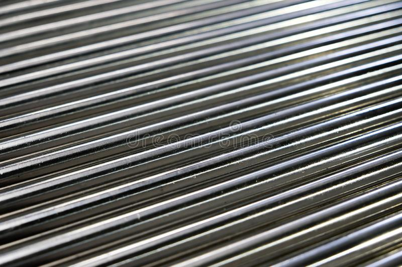Metal pipes, metal rods steel and iron. Close up shot of a ball bearing. Industrial roller bearing on a light background. Shallow stock photography