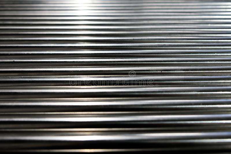 Metal pipes, metal rods steel and iron. Close up shot of a ball bearing. Industrial roller bearing on a light background. Shallow royalty free stock image