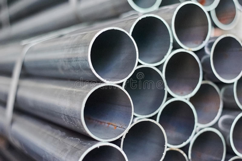 Metal pipes in a warehouse. Stacks of new round steel pipe. In factory stock photo