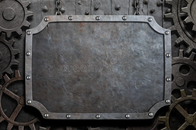 Metal plate hanging on chains over medieval gears royalty free stock photography