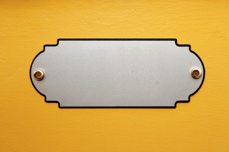 The metal plate on the wall. Yellow metal poster on the wall royalty free stock image