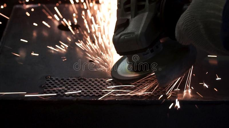 Metal polishing with a hand sander with a polishing disk. Clip. Factory worker at workshop grinding steel rod with stock photography