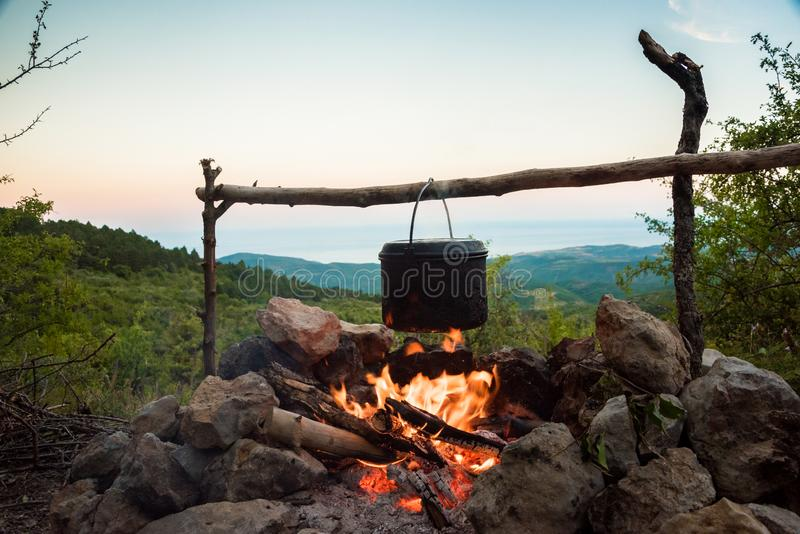 Cauldron hanging over campfire stock photos
