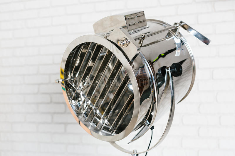 Metal projector on white brick wall. Background royalty free stock image