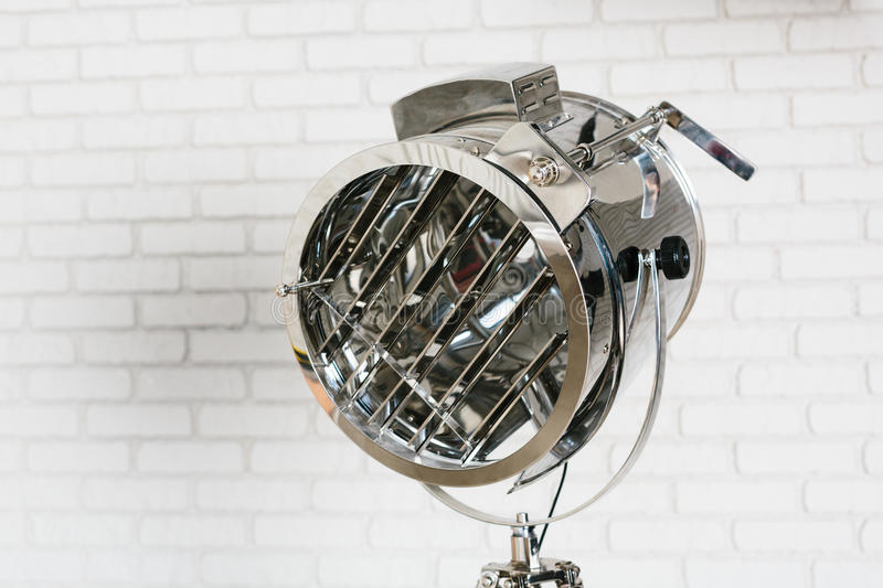 Metal projector on white brick wall. Background stock image