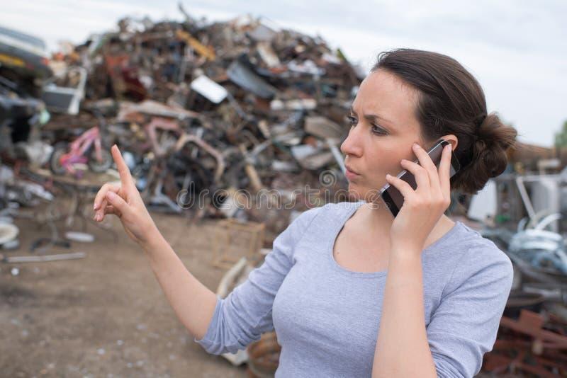 Metal przetwarza pracownika gestykuluje telefon komórkowego i używa przy junkyard obrazy stock