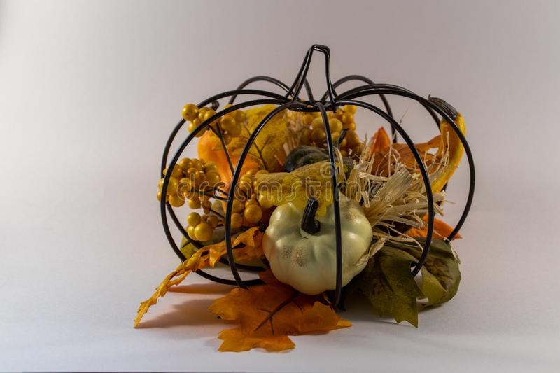 Metal pumpkin filled with fall decorations stock images