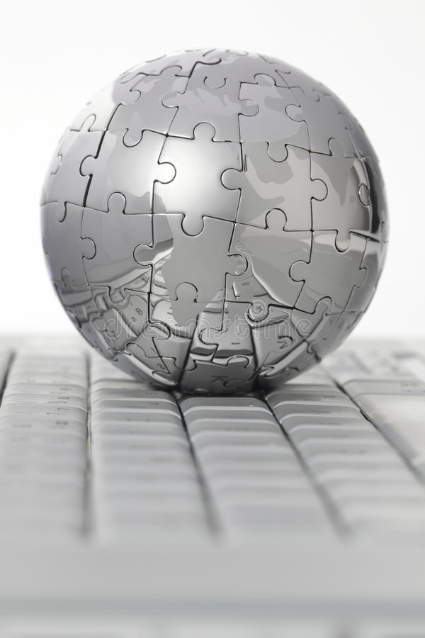 Metal puzzle globe on computer keyboard royalty free stock photography