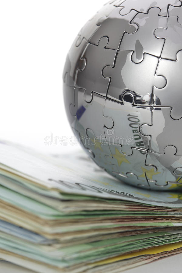 Metal puzzle globe with money royalty free stock images