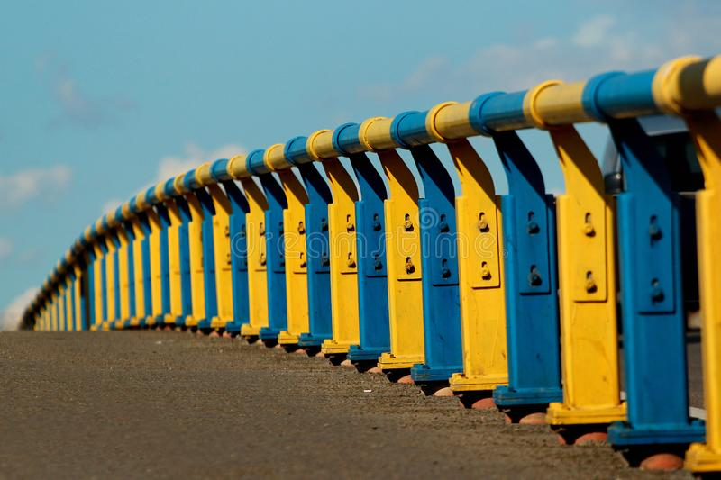 Metal railing on a bridge in Kyiv, Ukraine. Painted in yellow and blue colors of Ukrainian flag.  royalty free stock image