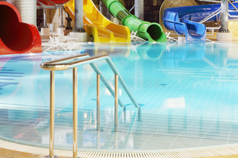 Metal railings, pool and multi-colored water slides royalty free stock image