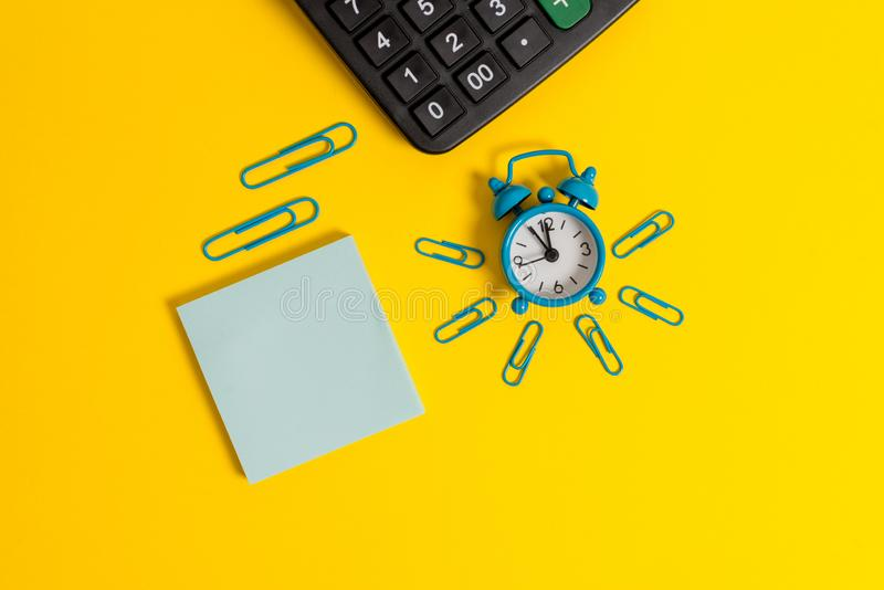 Metal retro vintage alarm clock wakeup clips calculator notepad sheet lying colored background empty text important stock photo