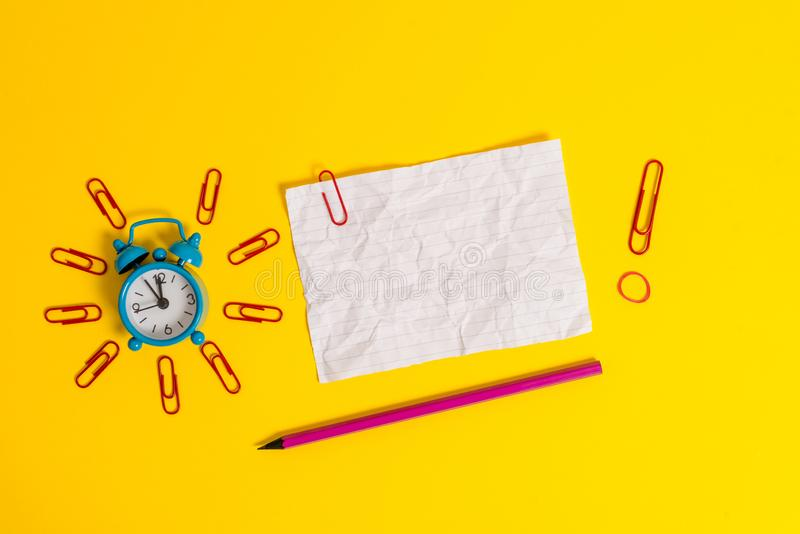 Metal retro vintage alarm clock wakeup clips crushed sheet note rubber band pencil lying colored background empty text. Metal alarm clock clips crushed sheet stock photos