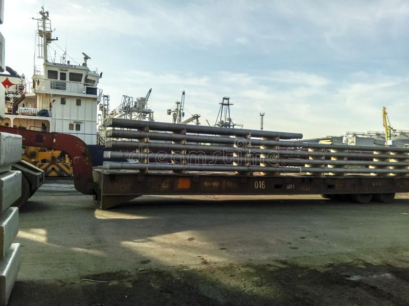 The metal rods folded on the port site for export. Temporary storage in the port of raw materials. Port cargo and cranes royalty free stock photo