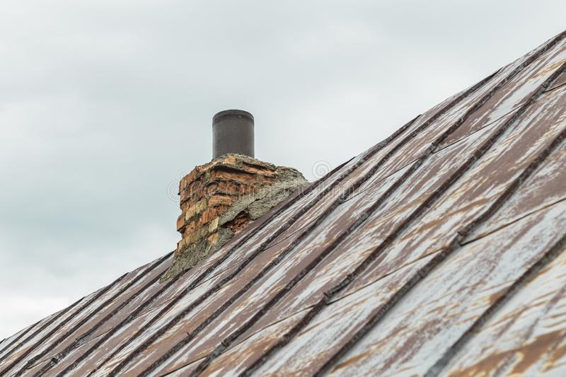 metal roof, the paint almost disappeared. on her chimney. trumpet and kerpich stock image