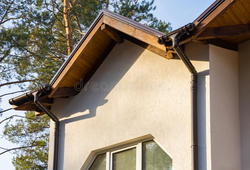 Metal roof with rain gutter on a part townhouse building under construction. Metal roof with rain gutter on a part townhouse building under construction stock images