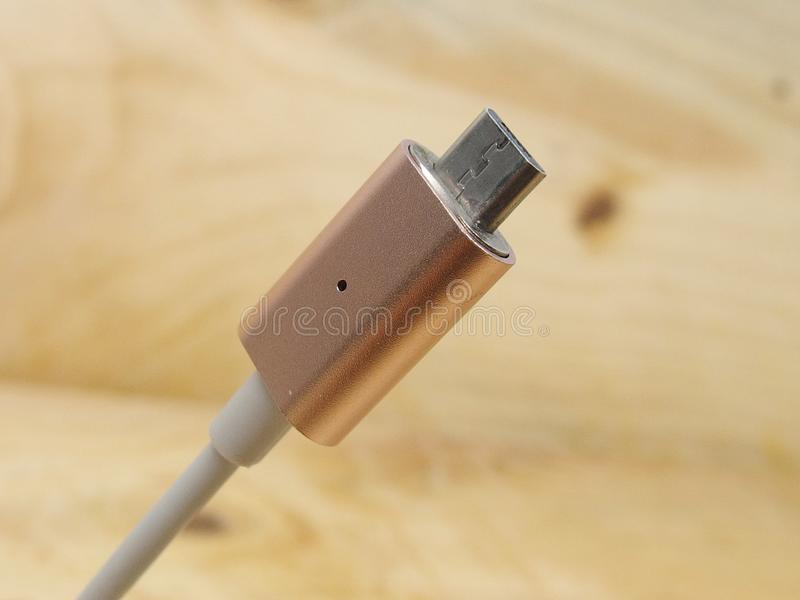 Micro usb adaptor. Metal rose gold usb data cable charger with magnetic adaptor on wood planks background stock photography