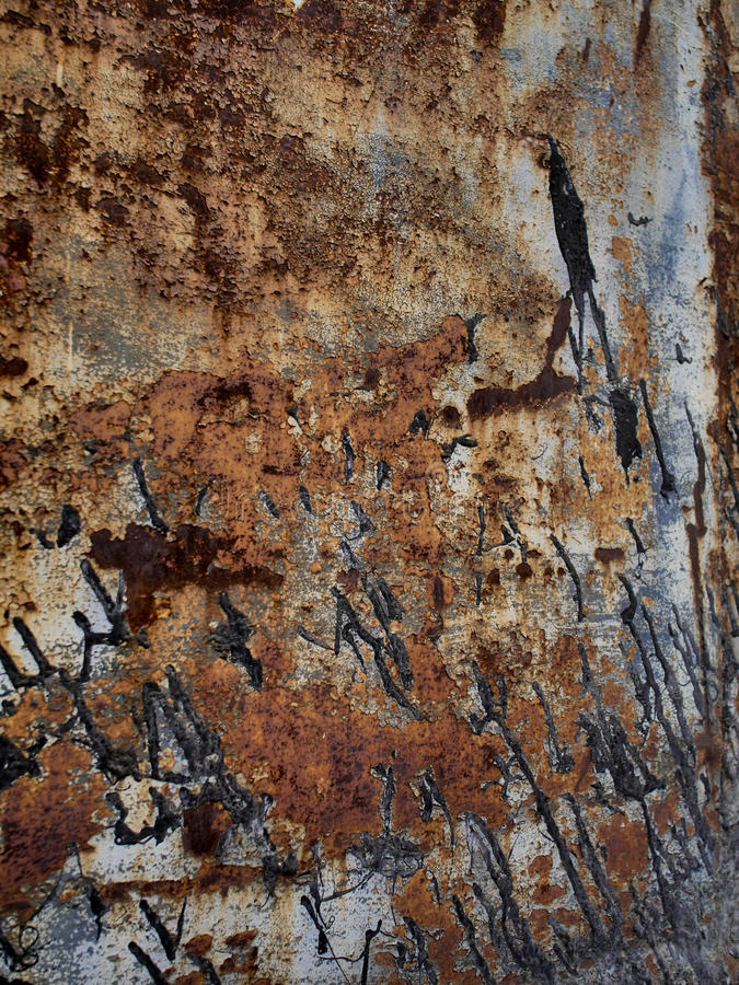 Pitted metal texture with black paint stains, abstract grunge background royalty free stock photography