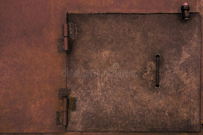 Metal rustic door hatch. Weathered vintage industrial surface with welding spots and rust. Dirty red rough pattern background stock photography