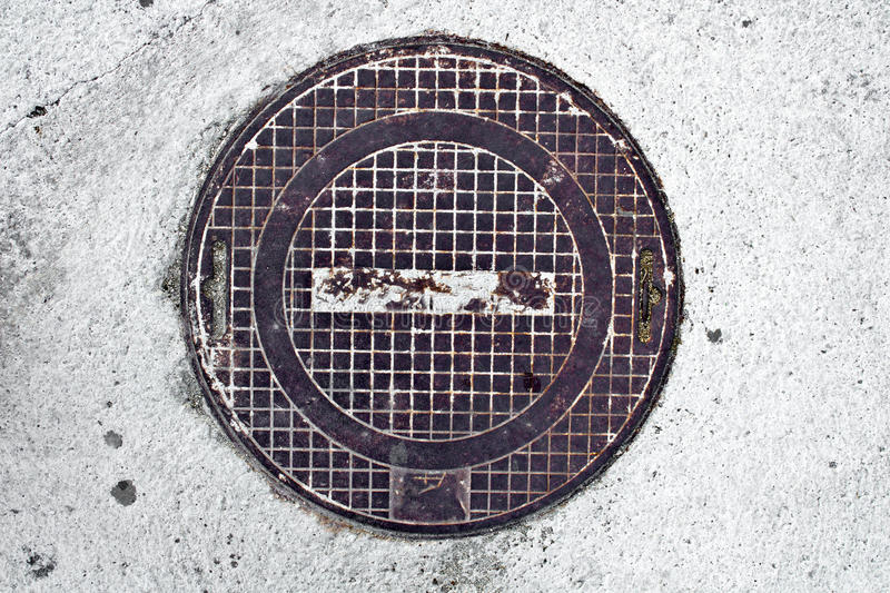 Metal rusty manhole cover in concrete stock photos