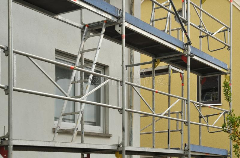 Metal scaffold at residential building under renovation. Metal scaffold with ladders at facade of a building under renovation stock photography