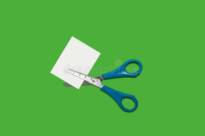 Scissors cutting small paper. Metal scissors with blue handles cutting small white memorandum paper lying on a green background . concept of office chancery royalty free stock photo