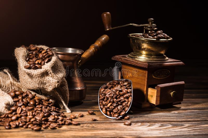 metal scoop, vintage cezve and coffee grinder on rustic wooden table spilled royalty free stock photo